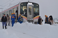 Passengers exit the rear end of a train stopped between stations due to snow, and walk along the tracks on the JR Shinetsu Line, in Sanjo, Niigata Prefecture, on Jan. 12, 2018. (Mainichi)