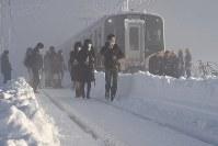 積雪で立ち往生したJR信越線の車両から降りて線路を歩く乗客ら=新潟県三条市で2018年1月12日午前8時18分、西本勝撮影