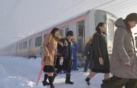 積雪で立ち往生したJR信越線の車両から降りて線路を歩く乗客ら=新潟県三条市で2018年1月12日午前8時21分、西本勝撮影