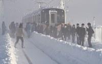 積雪で立ち往生したJR信越線の車両から降りて線路を歩く乗客ら=新潟県三条市で2018年1月12日午前8時15分、西本勝撮影