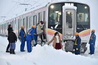 積雪で立ち往生したJR信越線の車両から降りて線路を歩く乗客ら=新潟県三条市で2018年1月12日午前6時49分、西本勝撮影