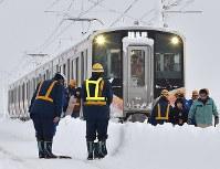 積雪で立ち往生したJR信越線の車両から降りて線路を歩く乗客ら=新潟県三条市で2018年1月12日午前6時58分、西本勝撮影