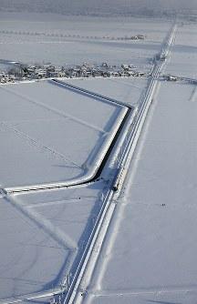 大雪の影響で立ち往生するJR信越線の車両(中央)=新潟県三条市で2018年1月12日午前7時58分、本社機「希望」から