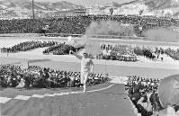 聖火台下で辻村いずみさんから聖火を受け取り、聖火台に向かって103段の階段を駆け上がる、聖火リレー最終ランナーの高田英基さん。高校1年生の16歳=北海道札幌市の真駒内スピードスケート競技場で1972年2月3日撮影