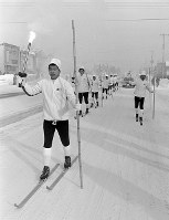 聖火リレー北海道北コース。吹雪の中、名寄市に入った聖火。開拓時代に使われた竹竿の1本杖スキーで進んだ=北海道名寄市で1972年1月23日撮影