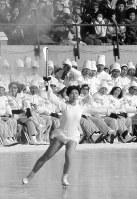 純白の衣装で、聖火を高く掲げて開会式に入場、リンクを回る辻村いずみさん。高校1年生の16歳=北海道札幌市の真駒内スピードスケート競技場で1972年2月3日、中村太郎撮影