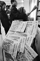 70メートル級ジャンプで日本が金銀銅メダルを独占したニュースを報じた臨時夕刊を求める人たち=札幌市内で1972年2月6日撮影