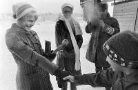 プレゼントされたこけしを手に、ファンの子どもと握手するジャネット・リン選手(米)=札幌市の選手村(真駒内団地)で1972年2月8日撮影