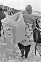 開会式会場の真駒内スピードスケート競技場スタンドでは観客に向け、防寒対策の座布団を売る人。1枚100円=札幌市の真駒内スピードスケート競技場で1972年2月3日撮影
