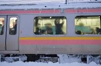 積雪で立ち往生したJR信越線の車両内で運行の再開を待つ乗客ら=新潟県三条市で2018年1月12日午前6時45分、西本勝撮影