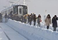 積雪で立ち往生したJR信越線の車両から降りて線路を歩く乗客ら=新潟県三条市で2018年1月12日午前8時10分、西本勝撮影