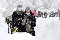 雪が降る中、大学入試センター試験の会場に向かう受験生たち=金沢市で2018年1月13日午前7時26分、平川義之撮影