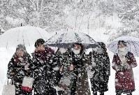 雪が降る中、大学入試センター試験の会場に向かう受験生たち=金沢市で2018年1月13日午前7時53分、平川義之撮影