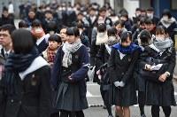 厳しい寒さの中、防寒着やマスクを身につけ試験会場へ向かう受験生たち=福岡市東区の九州大で2018年1月13日午前8時30分、矢頭智剛撮影