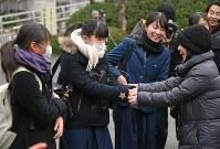 試験開始を前に高校の教諭(右)に激励される受験生たち=福岡市東区の九州大で2018年1月13日午前8時28分、矢頭智剛撮影