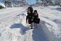 積雪で交通機関が乱れた影響で開始時間が1時間遅らされた新潟大学のセンター試験会場に向かう受験生たち=新潟市西区で2018年1月13日午前10時16分、和田大典撮影