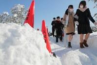 積雪で交通網が乱れた影響で、開始時間が1時間遅らされた新潟大学のセンター試験会場に向かう受験生たち=新潟市西区で2018年1月13日午前10時5分、和田大典撮影