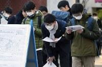 受験票などを見ながら試験会場を確認する受験生たち=東京都文京区の東京大学で2018年1月13日午前8時26分、渡部直樹撮影