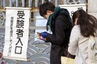 大学入試センター試験の会場の前で、参考書などを読みながら開門を待つ受験生たち=東京都文京区の東京大学で2018年1月13日午前7時49分、渡部直樹撮影