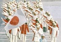 赤と白のユニホームで入場行進する日本選手団、旗手は益子峰行選手(29)。大観衆がスタンドを埋め尽くす中、35カ国・地域1128人の選手が入場行進した=真駒内スピードスケート競技場で1972年2月3日、大須賀興屹撮影