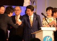 Prime Minister Shinzo Abe raises a toast at a gathering of his local support group, in Shimonoseki, Yamaguchi Prefecture, on Jan. 8, 2018. At right is Abe's wife Akie. (Mainichi)