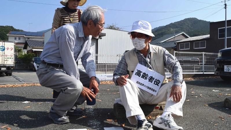 認知症声かけ訓練で、道に迷って座り込む高齢者役の男性に、目線を合わせて話し掛ける地域住民(左手前)=福岡市で