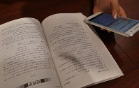 A university entrance exam taker uses a smartphone to look up contents of a textbook in Tokyo's Shinjuku Ward on Jan. 5, 2018. (Mainichi)