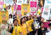 2015年に行われた大阪都構想の是非を問う住民投票で、「NO」と書かれたプラカードを手にパレードする有権者ら=大阪市で