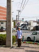 歴史ある日本最古のコンクリート電柱と写真に収まる須賀亮行さん=北海道函館市で2016年9月(須賀さん提供)