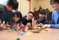 自宅で子どもたちとくつろぐ新川愛さん(中央)と修平さん(右)=神戸市長田区で2017年12月16日、久保玲撮影