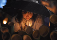A woman lights a bamboo lantern for victims of the 1995 Great Hanshin Earthquake while weeping in the rain at Higashi Yuenchi Park in Kobe's Chuo Ward early on the morning of Jan. 17, 2018. (Mainichi)