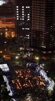 阪神大震災から23年。雨の中、発生時刻に黙とうする大勢の人たち=神戸市中央区で2018年1月17日午前5時46分、貝塚太一撮影