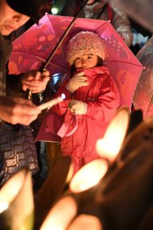 ろうそくの火を見つめる女の子=神戸市中央区の東遊園地で2018年1月17日午前5時56分、大西岳彦撮影