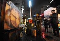 発生時刻で止まったままの時計の前で黙とうする人たち=兵庫県西宮市で2018年1月17日午前5時46分、平川義之撮影