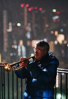 雨の中、夜明け前の神戸の街並みを背にトランペットを吹く松平晃さん=神戸市中央区で2018年1月17日午前6時7分、猪飼健史撮影