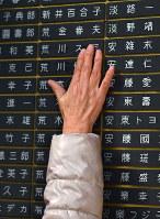 慰霊と復興のモニュメントで、銘板を触る女性=神戸市中央区の東遊園地で2018年1月17日午前7時39分、猪飼健史撮影