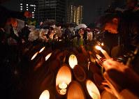 雨の中、竹灯ろうに火をつける人たち=神戸市中央区の東遊園地で2018年1月17日午前5時39分、川平愛撮影