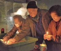 神戸市長田区の野田北部自治連合会が開いた最後の追悼式で、ろうそくに灯をともして犠牲者の冥福を祈る近隣住民たち=神戸市長田区の大国公園で2018年1月17日午前5時26分、黒川優撮影
