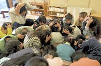 地震を想定した「シェイクアウト訓練」で頭を手で覆い、教室の中心に集まる園児たち=神戸市中央区で2018年1月17日午前10時3分、平川義之撮影