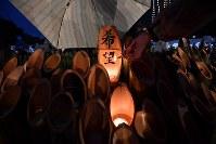 雨の中、竹灯籠に火をともす女性。「『希望』の火が消えたらいけない」と、傘を差しのべながら、火を絶やさぬようにと立っていた=神戸市中央区の東遊園地で2018年1月17日午前6時50分、川平愛撮影