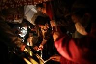 早朝から東遊園地を訪れ、雨の中、竹灯籠に火をともす人たち=神戸市中央区で2018年1月17日午前6時6分、貝塚太一撮影