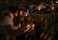 震災で祖母を亡くした茨城県つくば市のツアーコンダクター、白石美貴子さん(55)。震災時、イタリアに仕事で行っていて翌日パリで震災を知り号泣した。神戸市中央区の自宅近くに住む祖母が被災し、日ごとに衰弱していったという。「震災のことは忘れることはできない。その年に2人の兄に子どもが生まれ、彼らの成長を見るたびに震災からの年月を感じています」と語り、雨の中、竹灯籠に火をともした=神戸市中央区の東遊園地で2018年1月17日午前6時15分、貝塚太一撮影