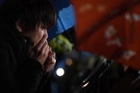 ろうそくを見つめる男性。しばらくその場を動かなかった=神戸市中央区の東遊園地で2018年1月17日午前6時34分、大西岳彦撮影