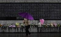 雨の中、犠牲者の名前が刻まれた慰霊碑を訪れた女性=兵庫県西宮市の西宮震災記念碑公園で2018年1月17日午前6時29分、久保玲撮影