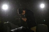 降りしきる雨の中、慰霊碑に向かって手を合わせる男性=兵庫県西宮市の西宮震災記念碑公園で2018年1月17日午前6時19分、久保玲撮影