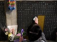 母親のために訪れたという女性は銘板をハンカチでそっとなぞった=神戸市中央区の東遊園地で2018年1月17日午前7時13分、平川義之撮影
