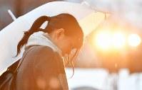 「慰霊と復興のモニュメント」を訪れた女性=神戸市中央区の東遊園地で2018年1月17日午前7時27分、猪飼健史撮影