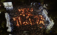 阪神大震災から23年。竹灯ろうの火で浮かび上がった1.17の文字を囲み雨の中、発生時刻に黙とうする大勢の人たち=神戸市中央区で2018年1月17日午前5時46分、貝塚太一撮影