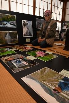 展示予定の写真を眺める三浦さん=由利本荘市前郷で