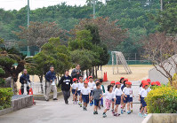 Children at Futenma No. 2 Elementary School in Ginowan, Okinawa Prefecture, walk to the school building during an evacuation drill on Jan. 18, 2018. (Mainichi)